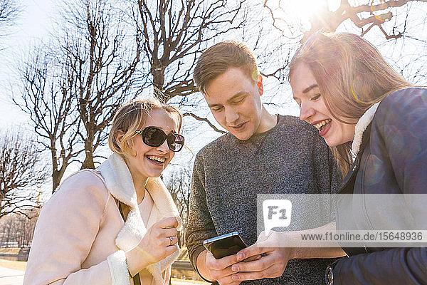 Freunde nutzen Smartphone in der Stadt