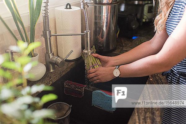 Frau wäscht Artischocken unter dem Küchenwasserhahn