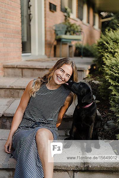 Haushund leckt Frau auf Gartentreppe