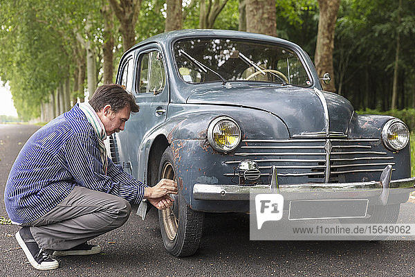 Man fixing tyre of vintage car on country road