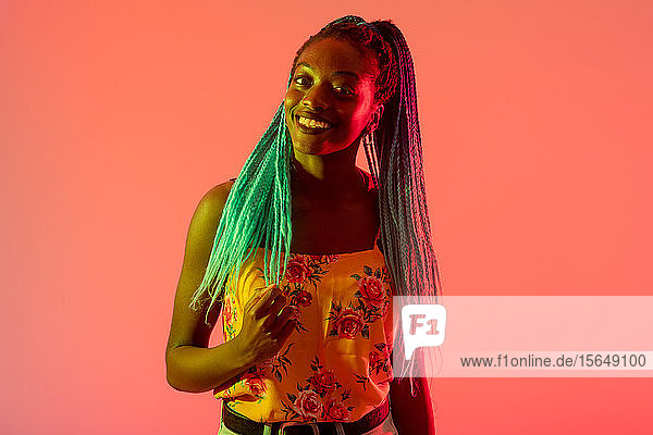 Woman posing against peach background