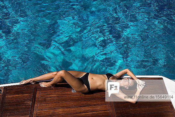 Frau im Bikini entspannt auf Yacht