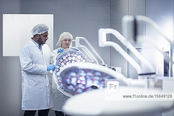 Arbeiter im Reinraum bei der Montage der OP-Beleuchtung in einer Fabrik für Elektronikmontage