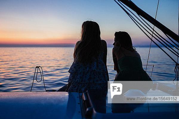 Freunde beobachten Sonnenuntergang auf einem Segelboot  Italien