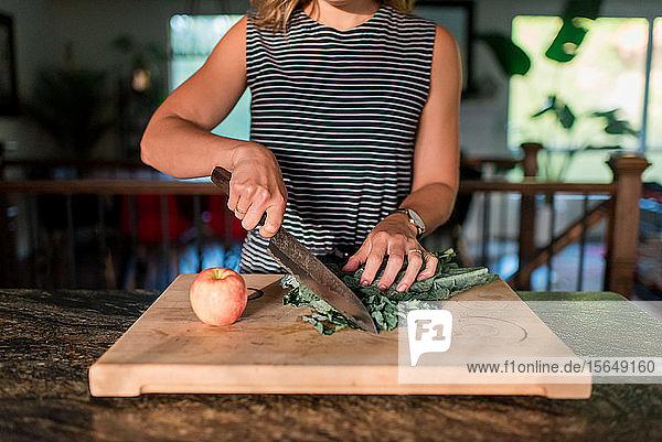 Frau schneidet frisches Gemüse auf Schneidebrett