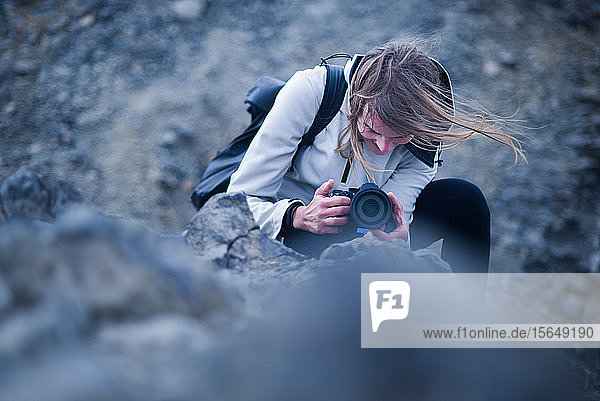 Female photographer kneeling to take photograph  Landmannalaugar  Iceland