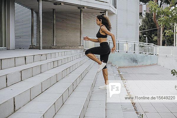 Junge Frau joggt die Treppe hinauf