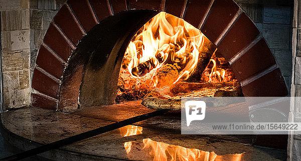 Pizza wird aus dem Steinofen entfernt