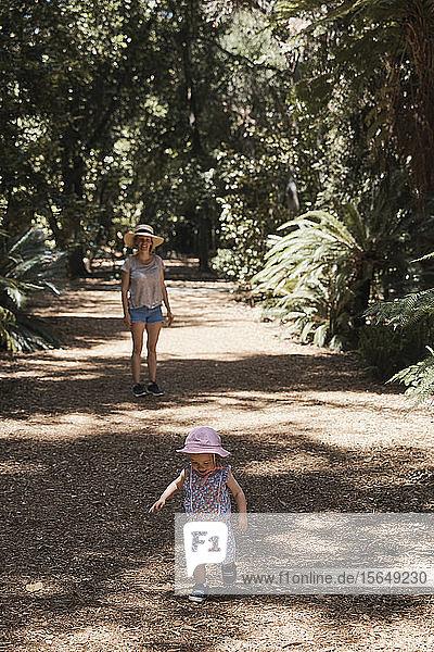 Mutter und kleines Mädchen gehen durch den Wald spazieren