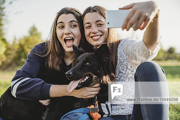 Schwestern beim Selbstausführen mit Hund im Park