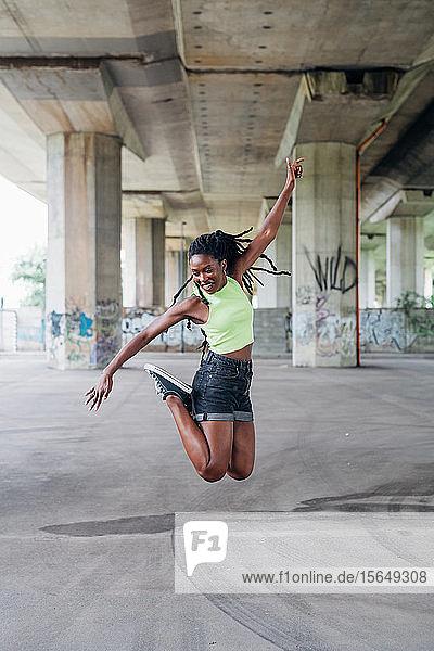 Frau springt in der Stadt in die Luft