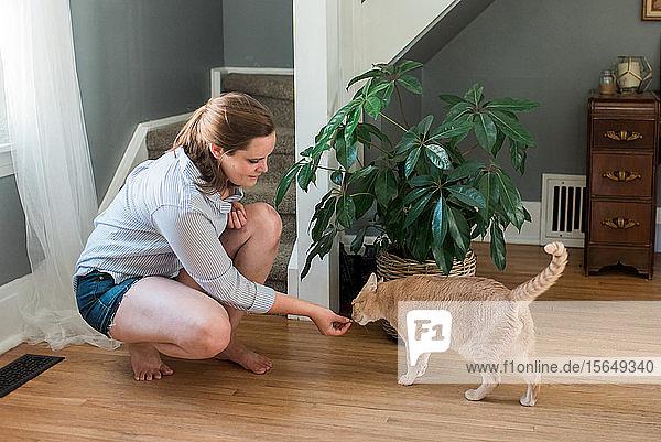 Frau füttert Katze zu Hause