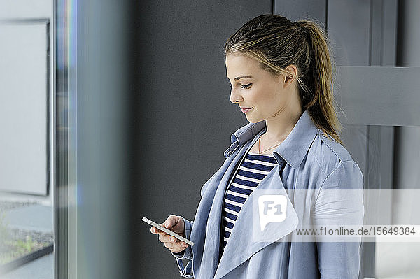 Female student using smartphone at corridor of office building