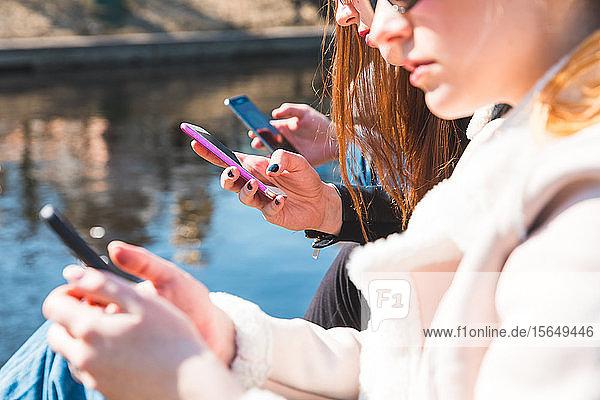 Freunde nutzen Smartphone am Fluss