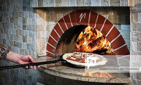 Koch legt Pizza in Steinofen