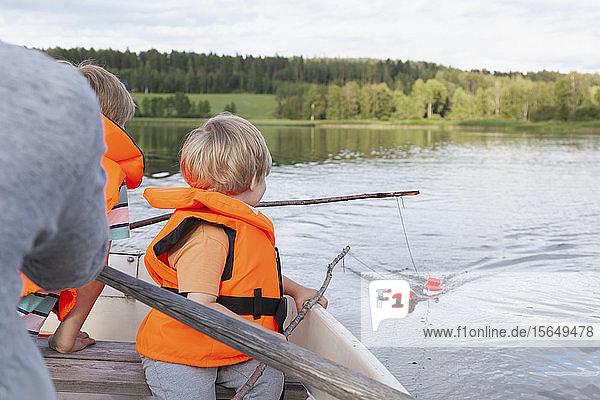 Erwachsener segelt mit Jungen auf einem Boot auf dem See  Finnland Erwachsener segelt mit Jungen auf einem Boot auf dem See, Finnland