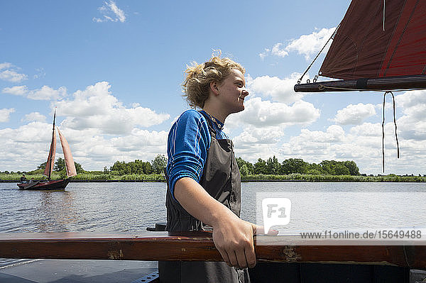 Girl stands at helm of large flat-bottom traditional sailing ship