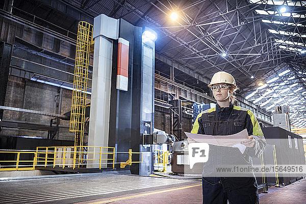 Arbeitnehmerin mit spezialisierter großer 3D-CNC-Drehmaschine in einem Stahlwerk