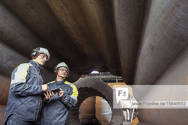 Arbeiter mit digitalem Tablett  das die Innenseite der Form in Stahlwerken inspiziert