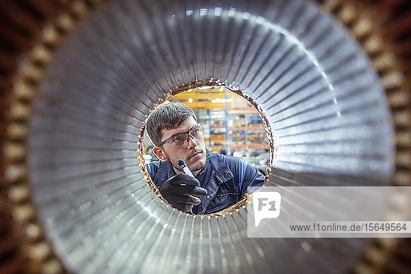 Apprentice electrical engineer inspecting winding on generator stator in electrical engineering factory