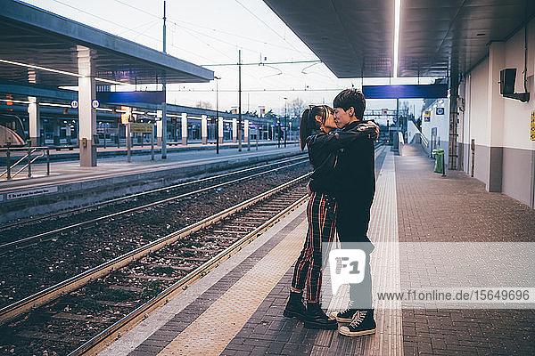 Junges Paar küsst sich auf dem Bahnsteig eines Bahnhofs  Mailand  Italien