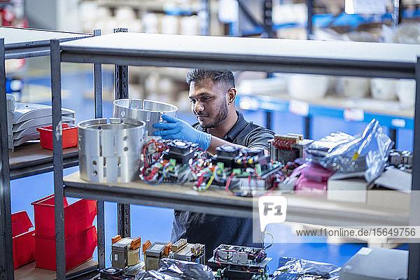Arbeiter bei der Kommissionierung von Produkten aus dem Lager in einer Elektronik-Montagefabrik