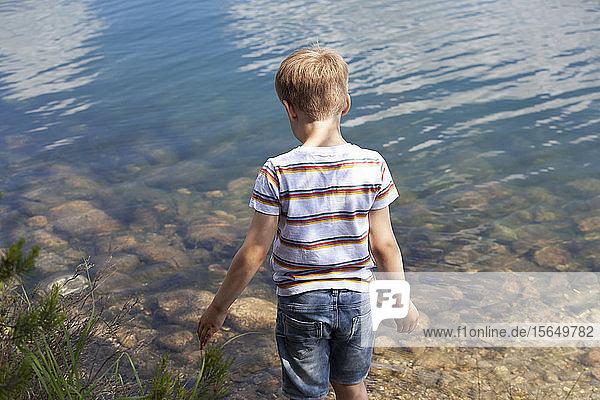 Boy playing near lake