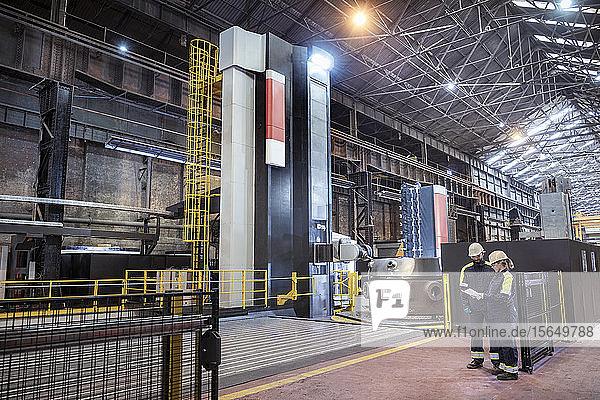 Arbeiter mit spezialisierter großer 3D-CNC-Drehmaschine in einem Stahlwerk