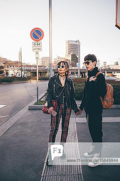 Junges Paar hält Händchen und wartet auf der Straße  Mailand  Italien