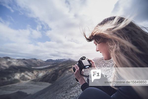 Female photographer with wind blown hair taking photograph on edge of volcano  Landmannalaugar  Iceland