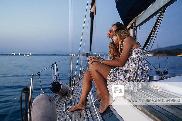 Enge Freunde entspannen abends auf einem Segelboot  Italien