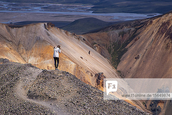 Frau fotografiert vom Hügelkamm aus  Landmannalaugar  Island