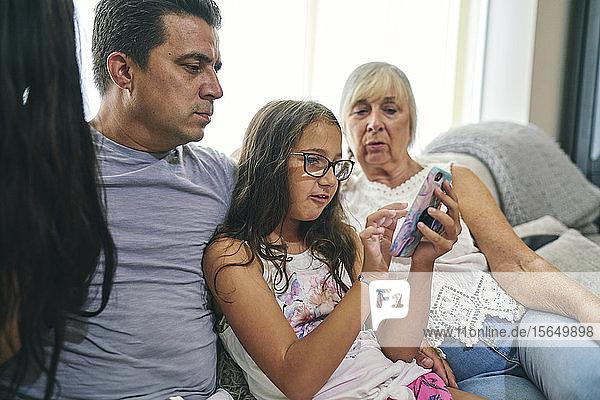 Drei-Generationen-Familie genießt Computerspiele auf dem Sofa