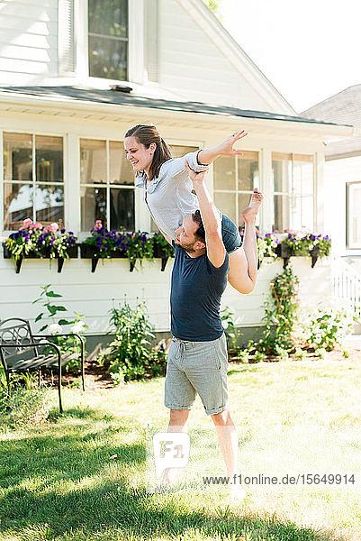 Frau fliegt auf der Schulter eines Mannes im Garten