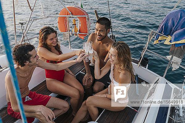 Freunde stoßen mit Champagner auf einem Segelboot an  Italien