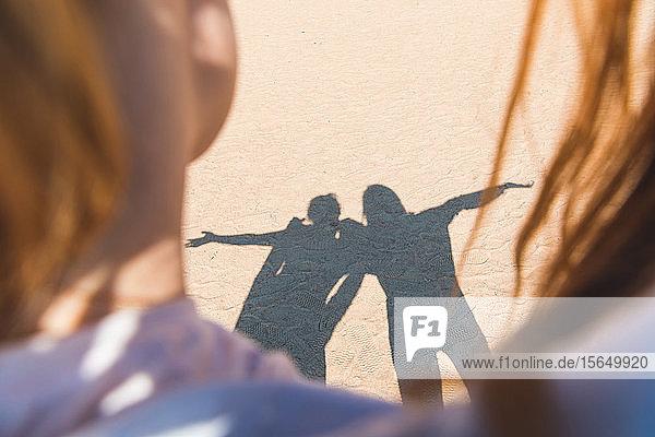 Schatten von zwei Personen auf Sand