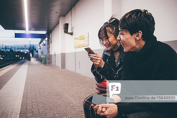 Young couple sharing text on train platform  Milan  Italy
