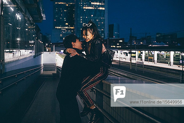 Young couple laughing and hugging in train station  Milan  Italy