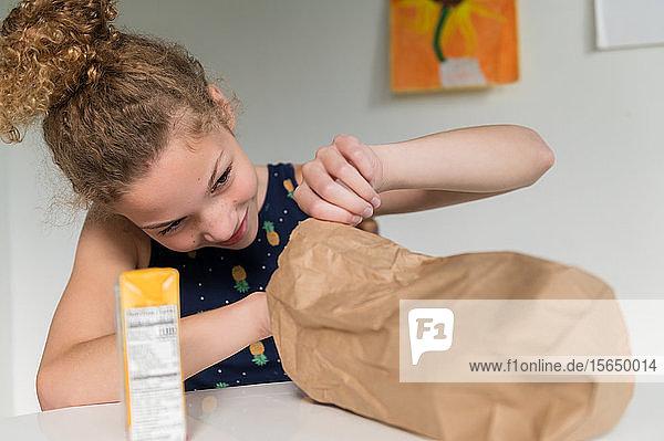 Mädchen schaut in braune Papiertüte