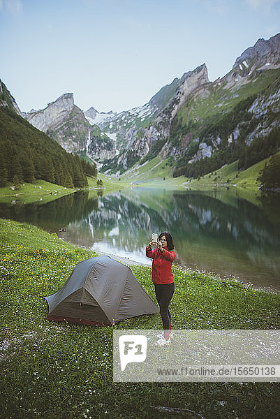 Woman taking photograph by tent near Seealpsee lake in Appenzell Alps  Switzerland
