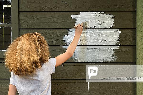 Mädchen malt Haus