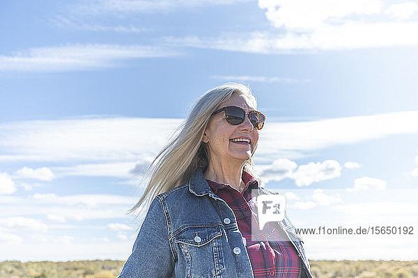 Woman wearing sunglasses against cloud