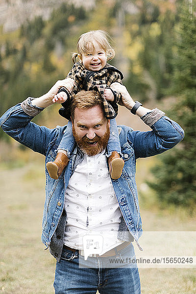 Father carrying his daughter on his shoulders by forest