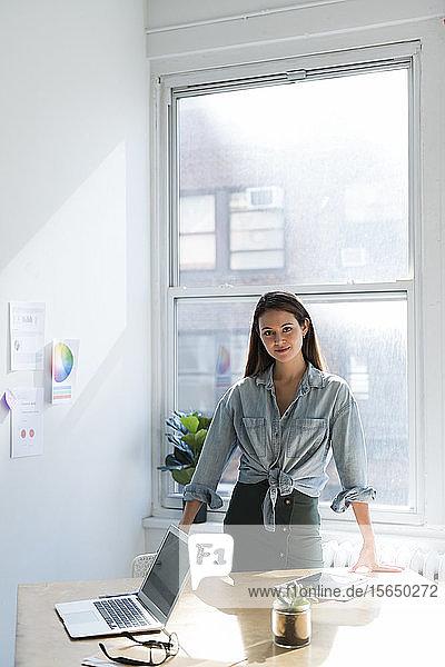 Geschäftsfrau stehend hinter Bürotisch