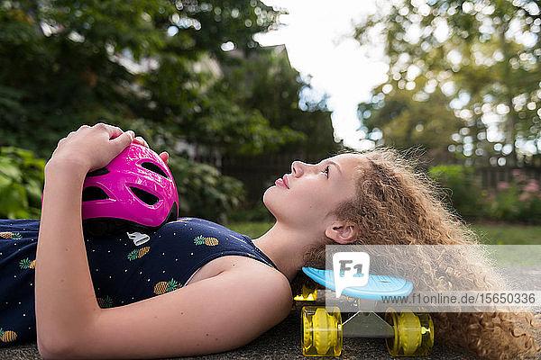 Mädchen liegend auf Skateboard