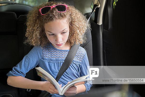 Mädchen liest Buch im Auto