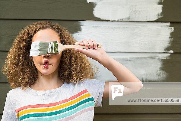 Mädchen bedeckt ihre Augen mit einem Pinsel