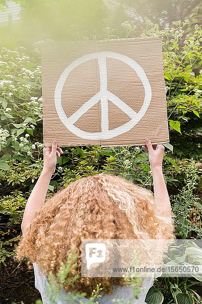 Mädchen hält Schild mit Friedenssymbol