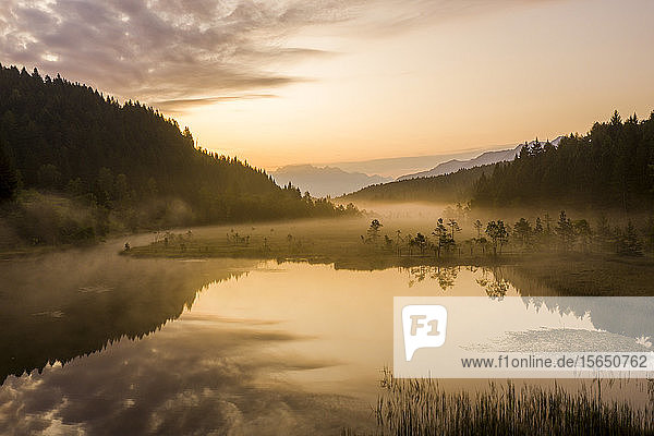 Sky painted orange at dawn with misty land of Pian di Gembro nature Reserve  aerial view  Aprica  Valtellina  Lombardy  Italy