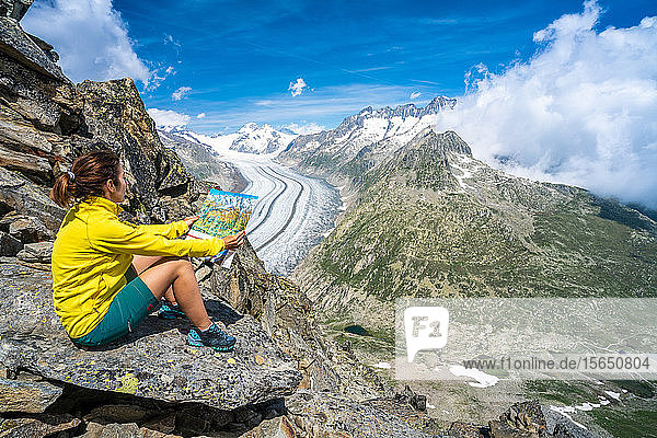 Woman looking at map sitting on rocks at Eggishorn viewpoint above Aletsch Glacier  Bernese Alps  canton of Valais  Switzerland